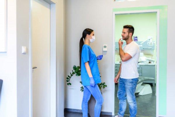 Uma mulher conversando com um homem que está com a mão sinalizando dor no dente