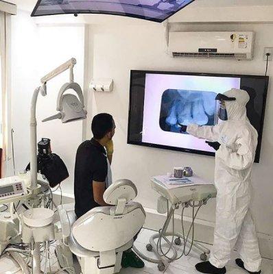 Um dentista utilizando tecnologia para mostrar um tratamento dentário