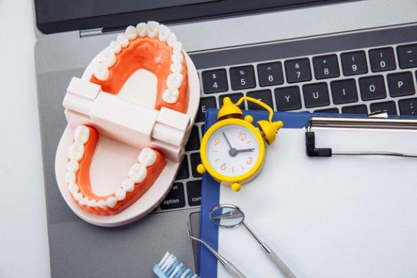 dentadura, relógio, um computador e uma prancheta