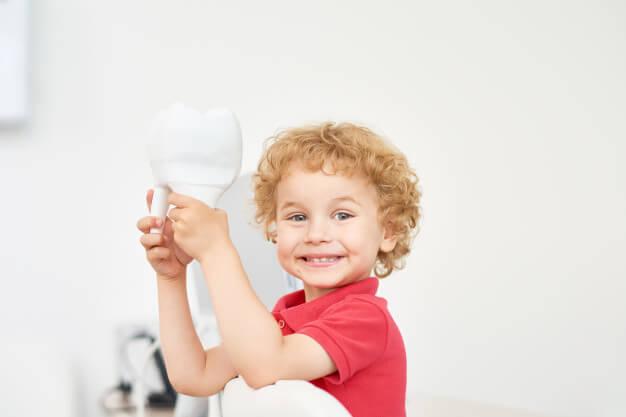 Criança sorrindo em consultório segurando o dente