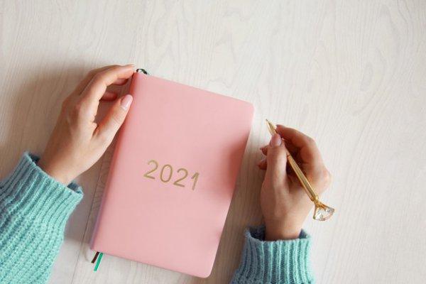 Pessoa com uma agenda rosa do ano de 2021